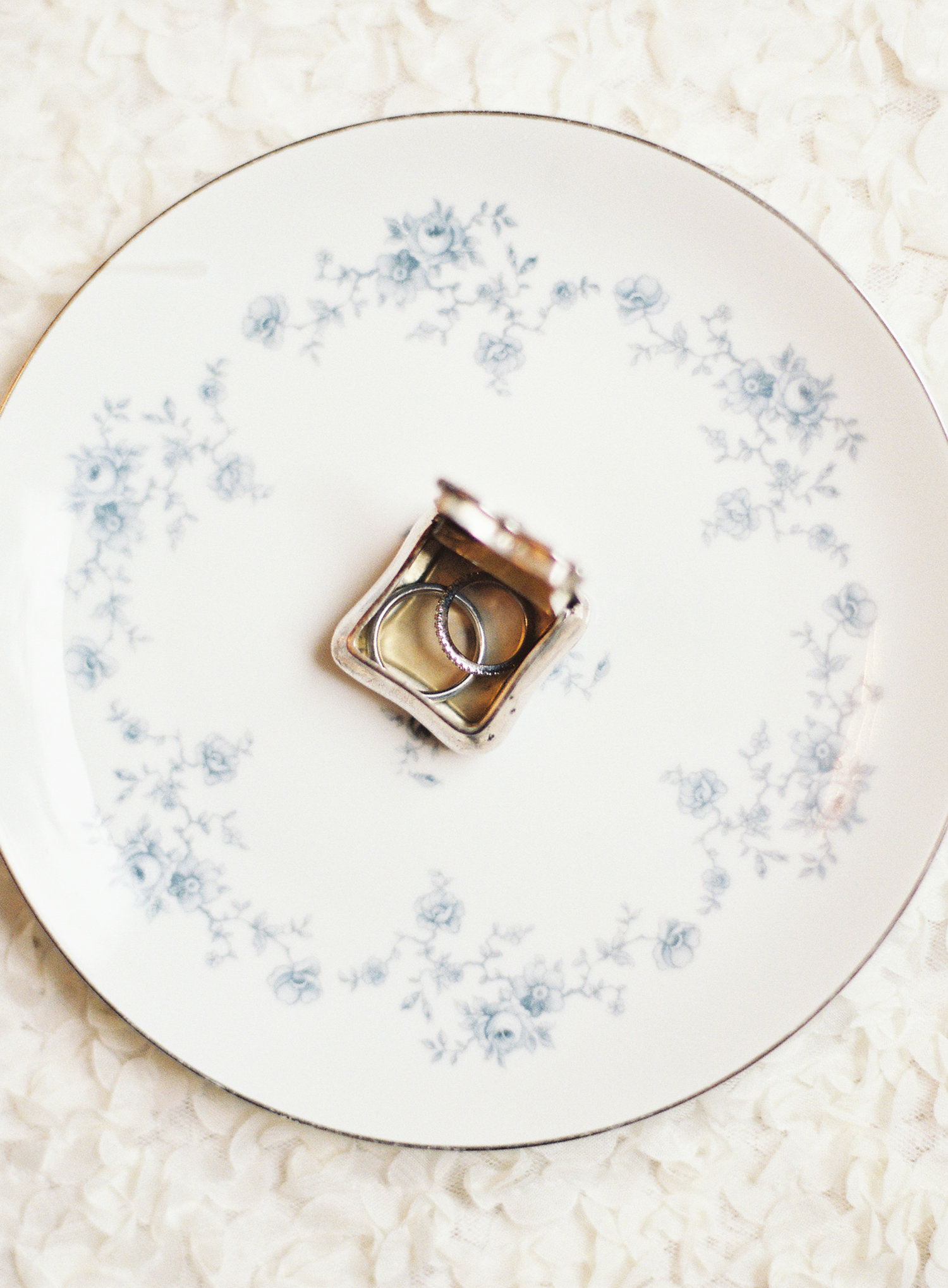 wedding rings in a gold box on top of a white and blue china plate
