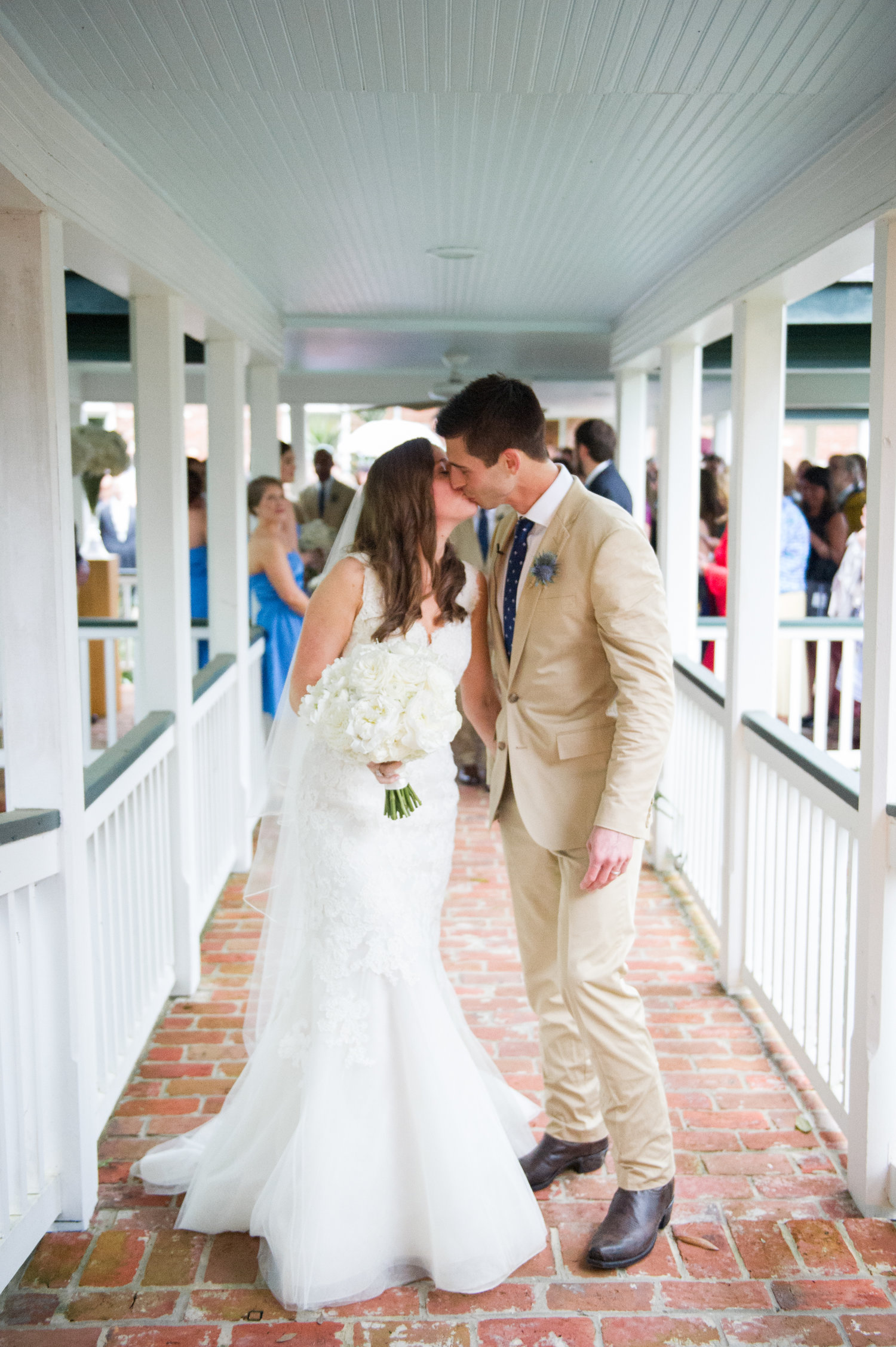 Bride and Groom kiss under a white walkway in front of their guests