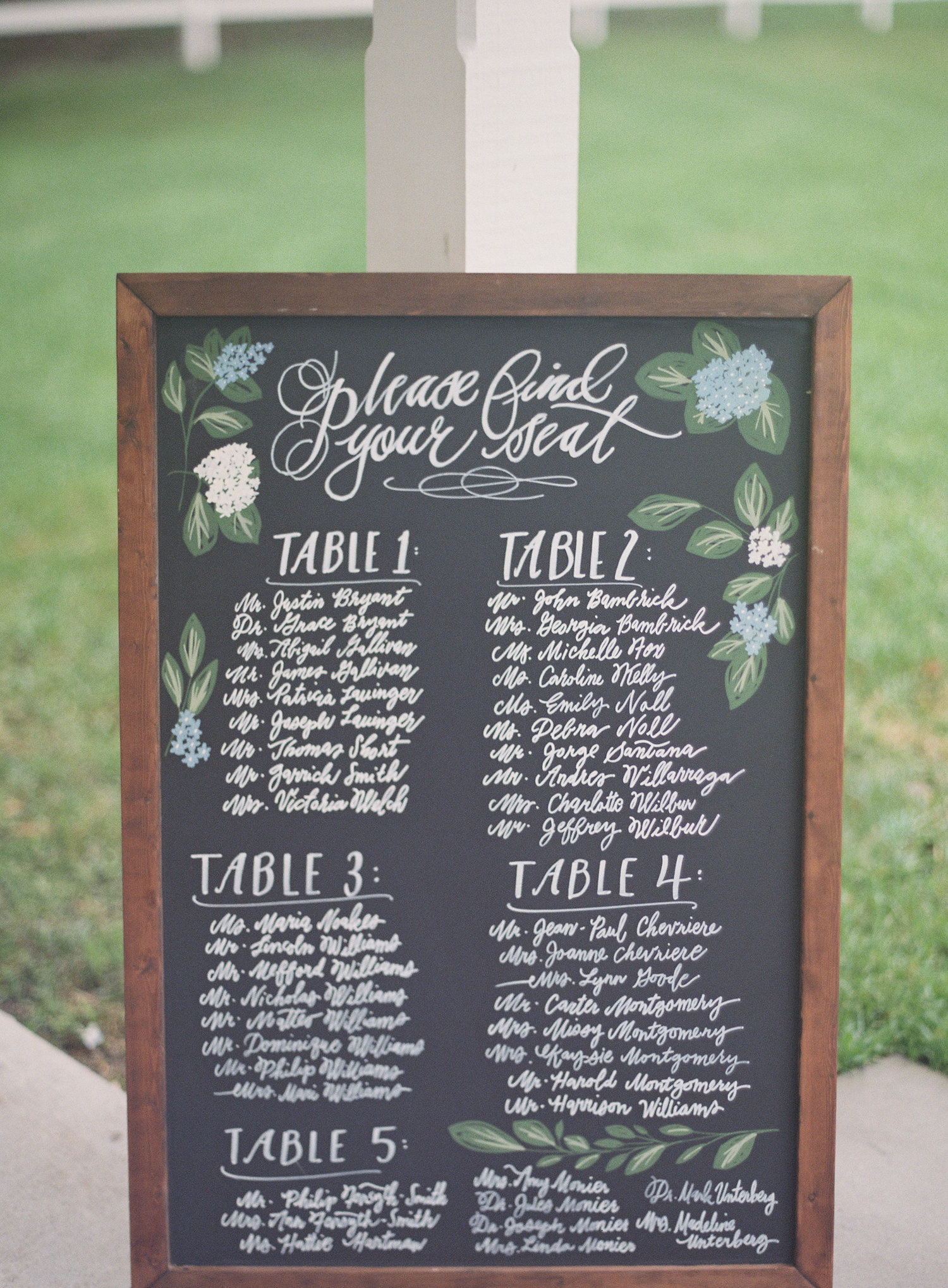 Chalk board painted with table seating for the wedding with flowers drawn around the names