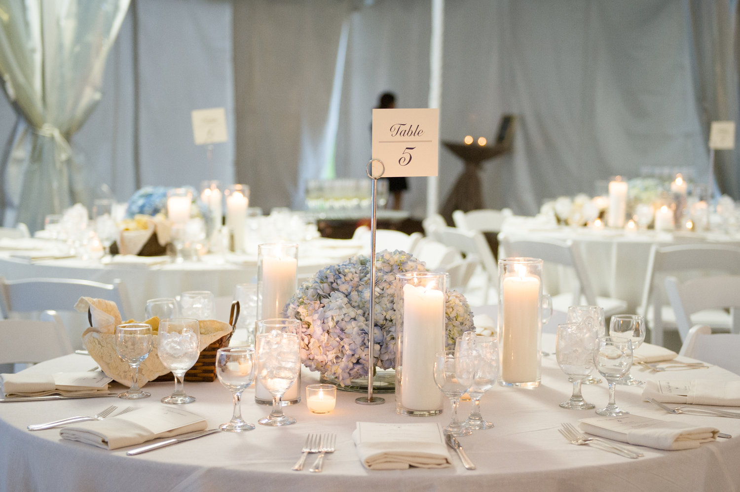tall table numbers with white linens and baby blue hydrangeas on a circle table