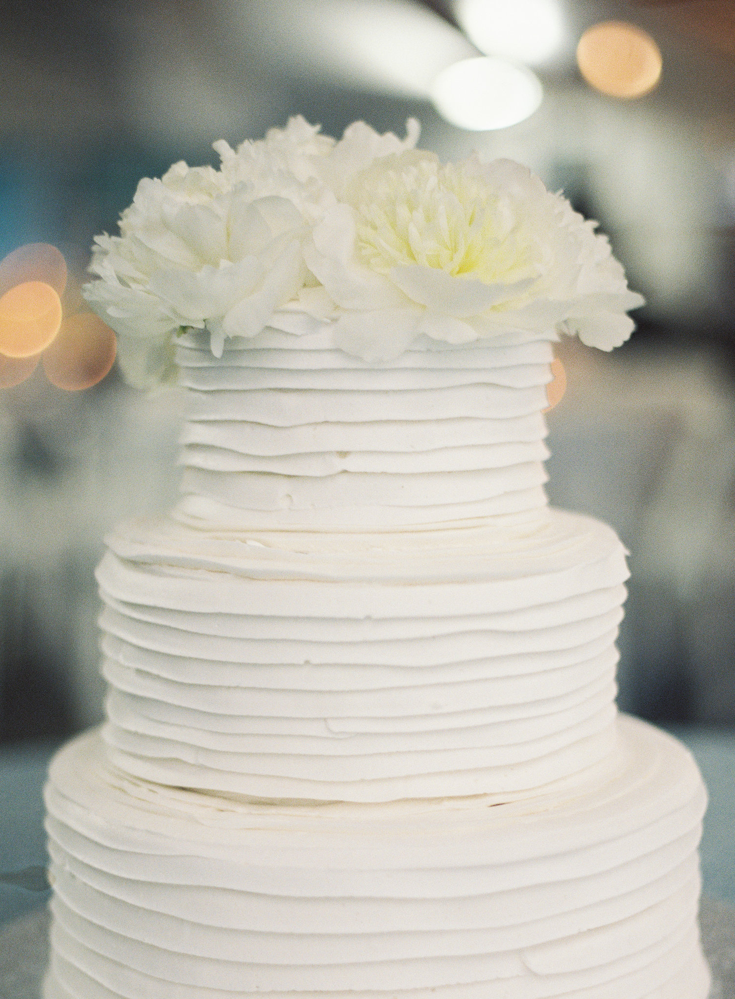 3 tier white cake with white flowers on the top of the cake