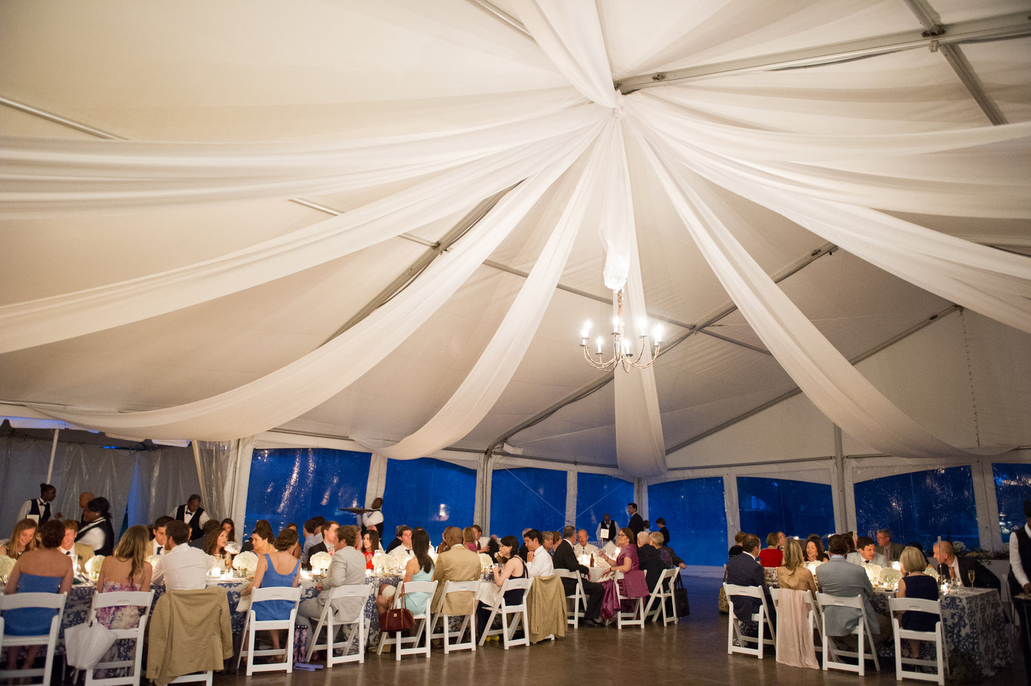 white closed in tent with white tulle cascading from the ceiling at a wedding reception