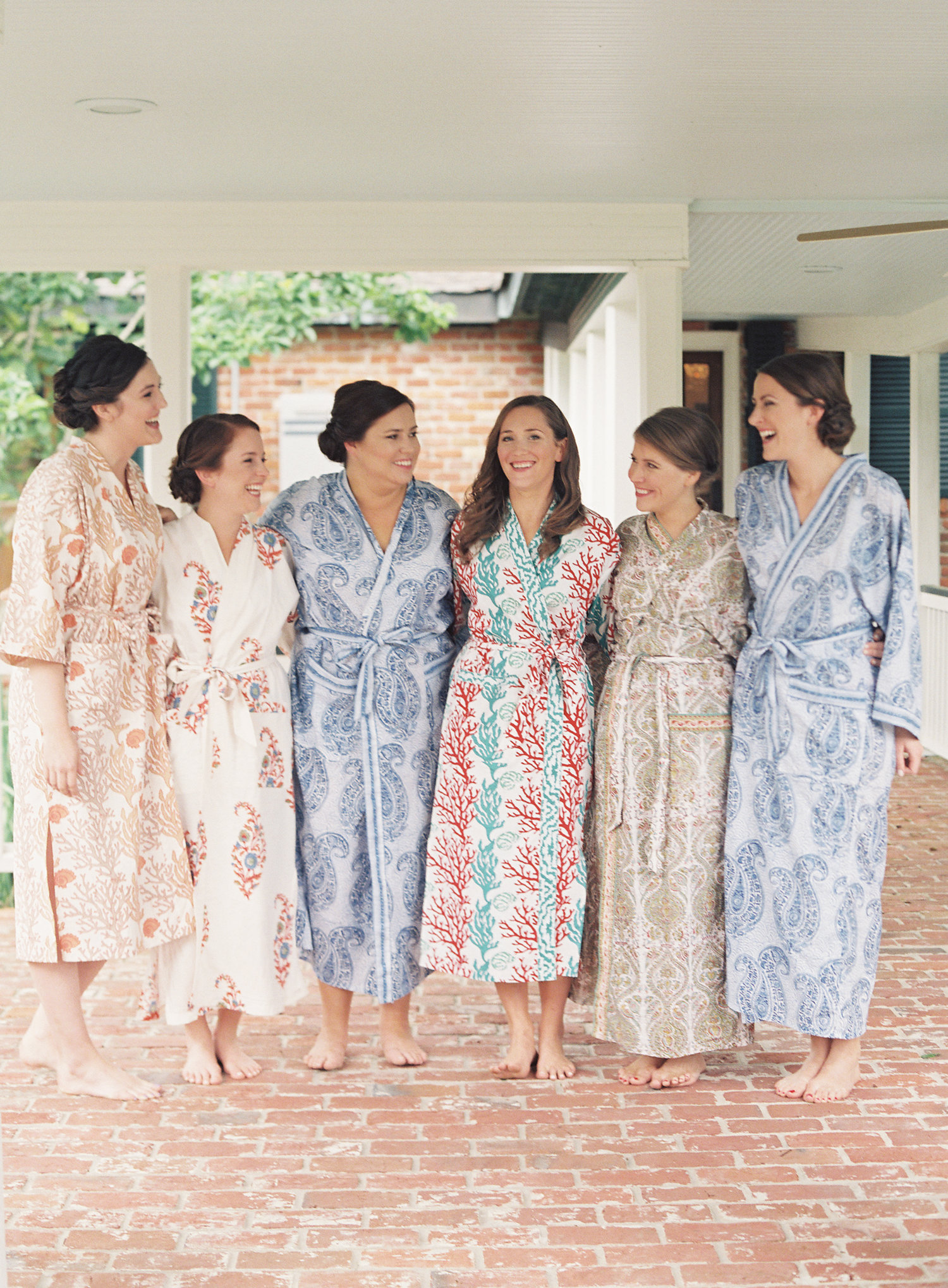 Bride and bridesmaids smile in their robes after getting dressed