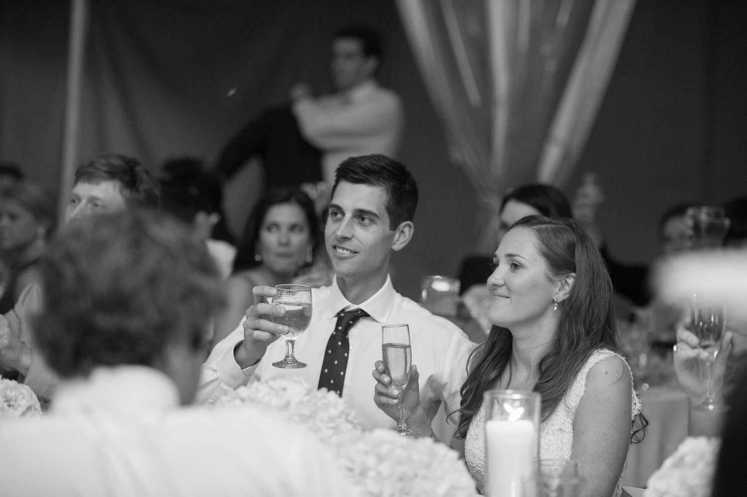 black and white photo of the bride and groom raising a glass white guests make toasts
