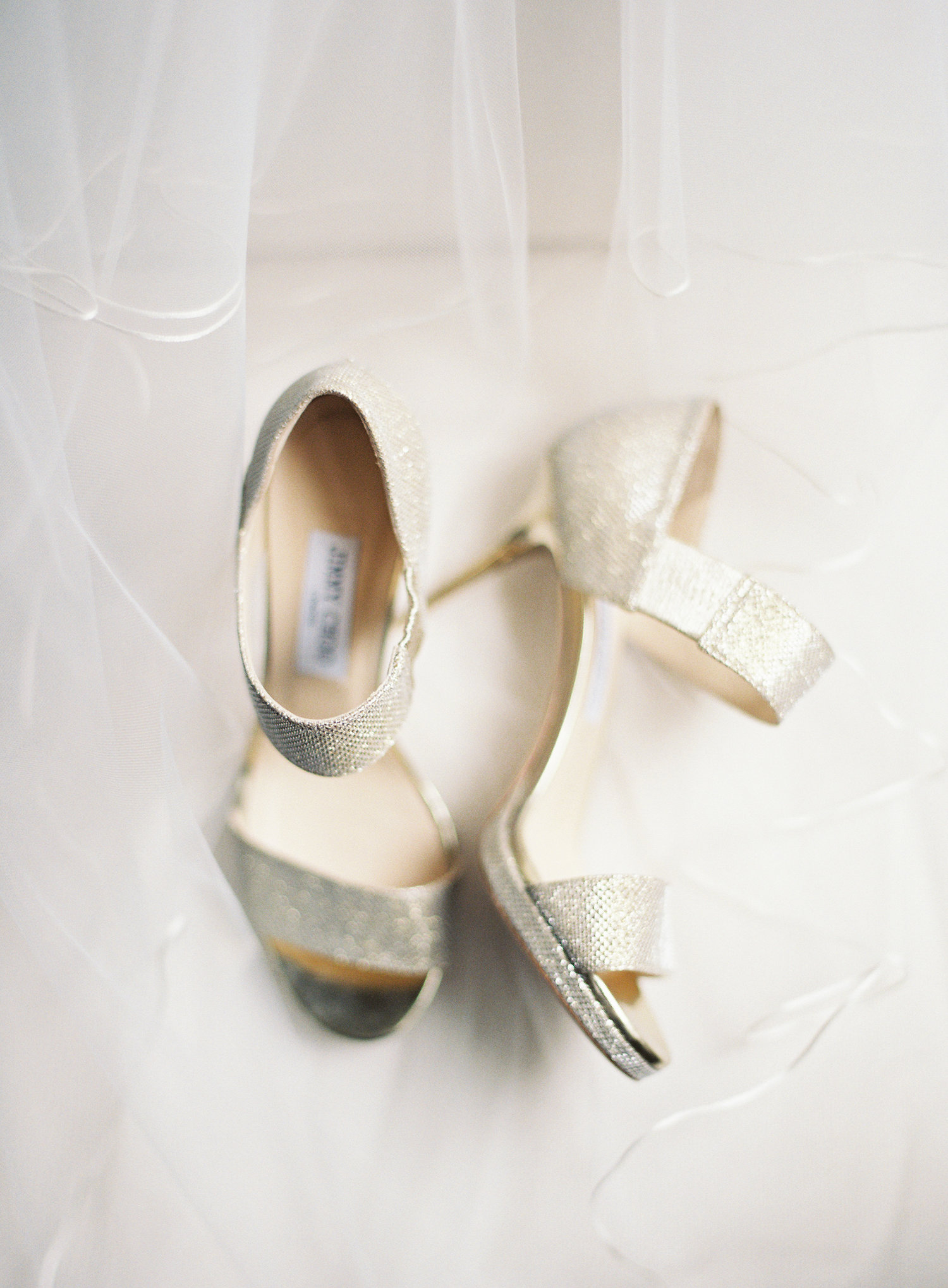 sparkly gold pumps next to the white train of a wedding gown