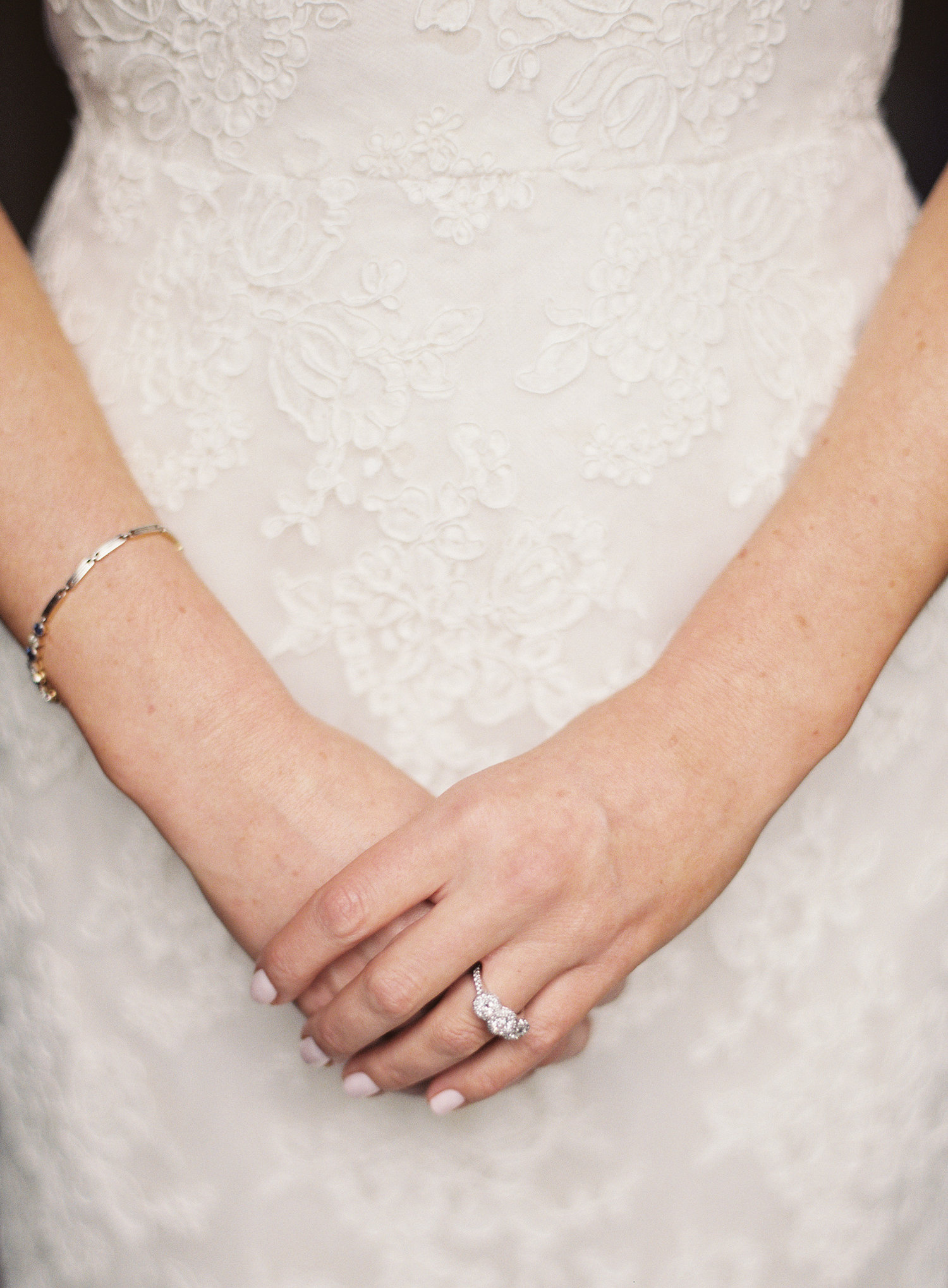 close up photo oh brides stitching on her wedding gown and her gorgeous three stone engagement ring