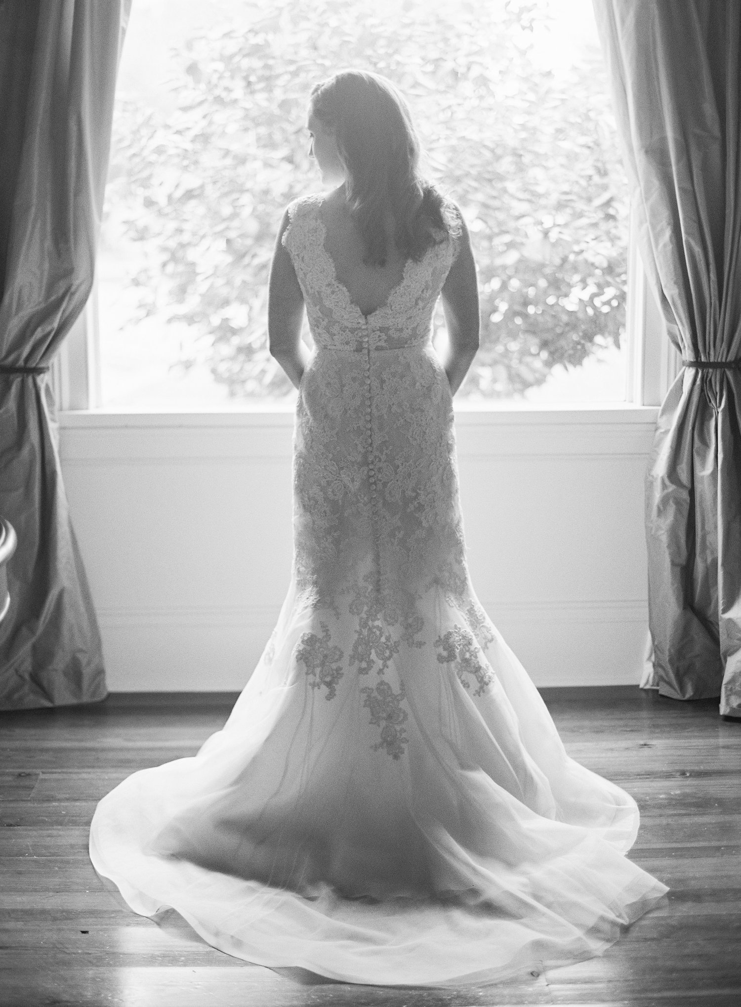 black and white photo of a bride in her wedding dress looking out the window