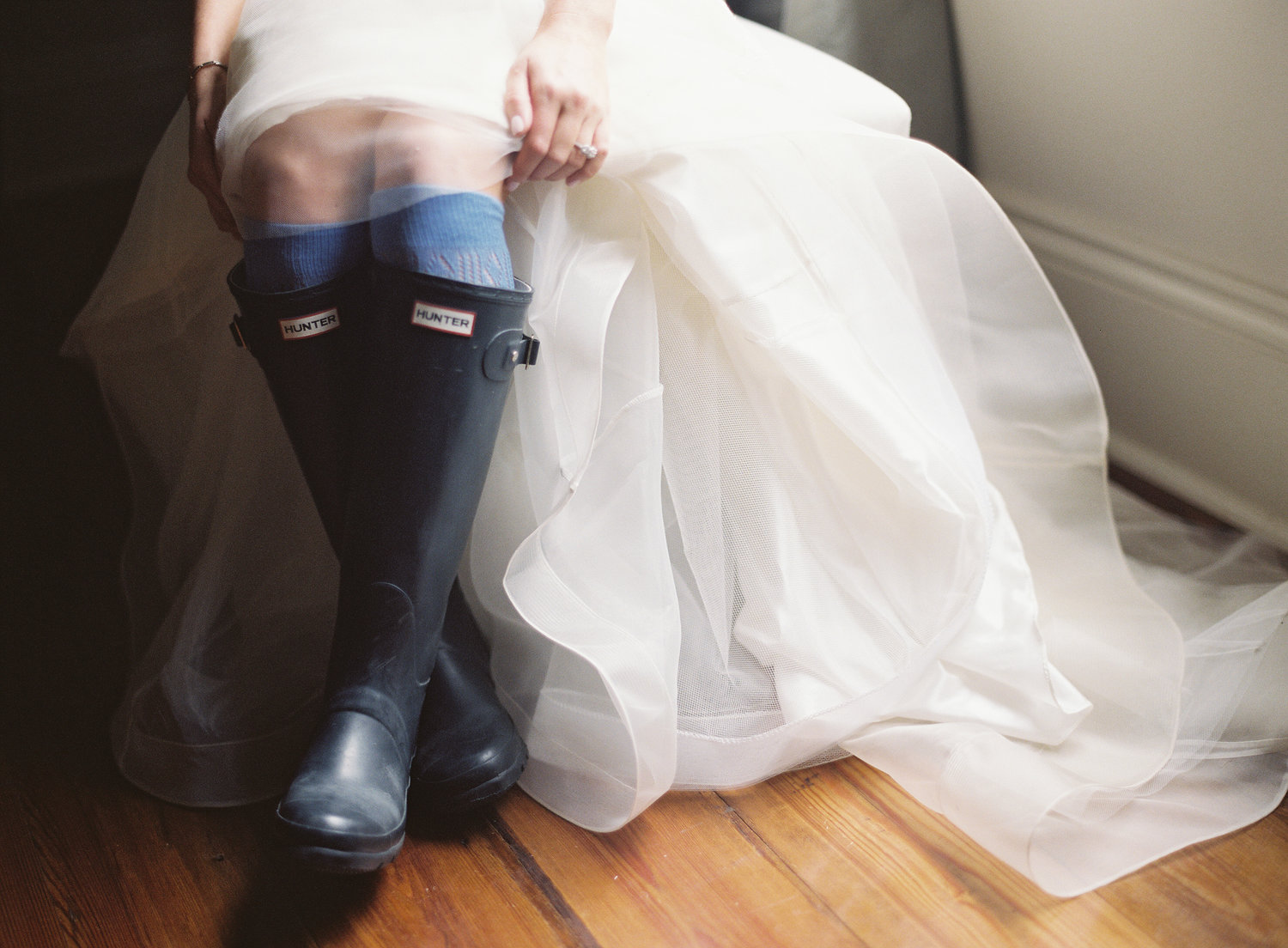 Bride in her wedding dress showing her black hunter rain boots under the dress