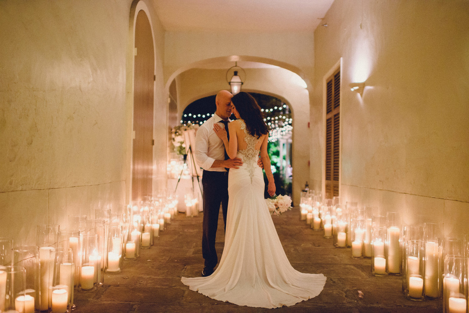 newlyweds embrace in carriageway of a courtyard surrounded by hundreds of candles in wedding gown and suit