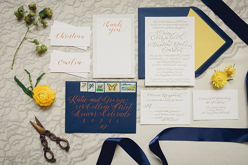 detail of invitation with blue envelope, copper calligraphy, and yellow florals on a lace background