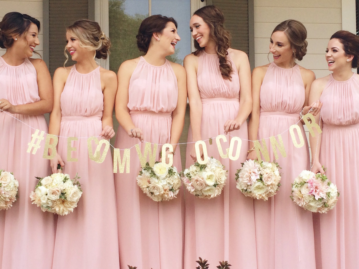 group of bridesmaids in pink dresses and white and blush bouquets looking at each other and laughing