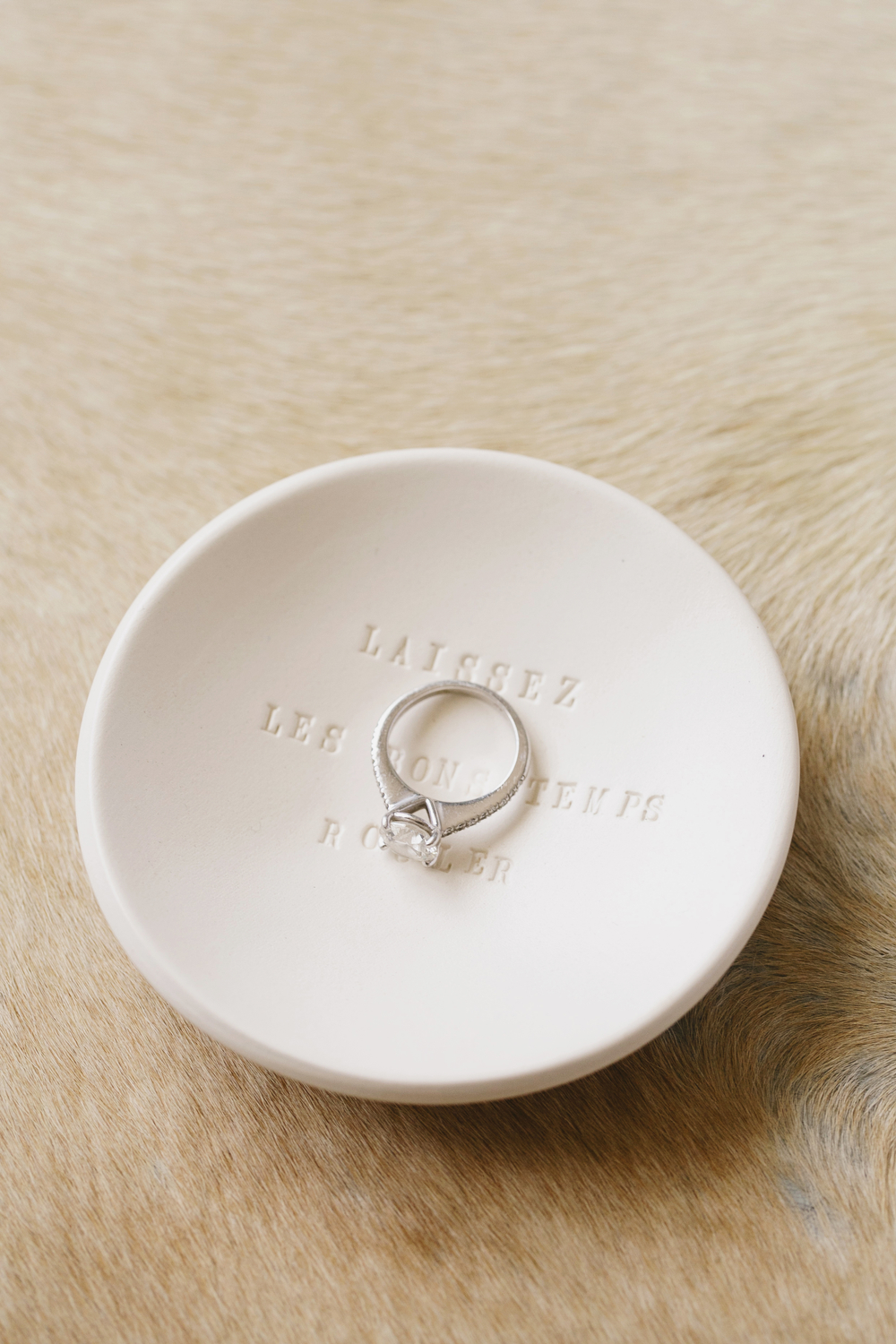 detail of diamond engagement ring in white ceramic ring dish withe typed letters on a cowhide rug background