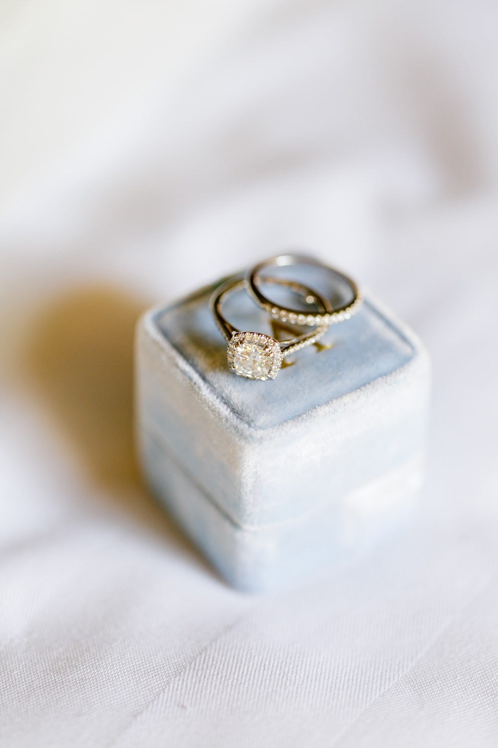 detail of diamond engagement ring and wedding band on top of velvet ring box