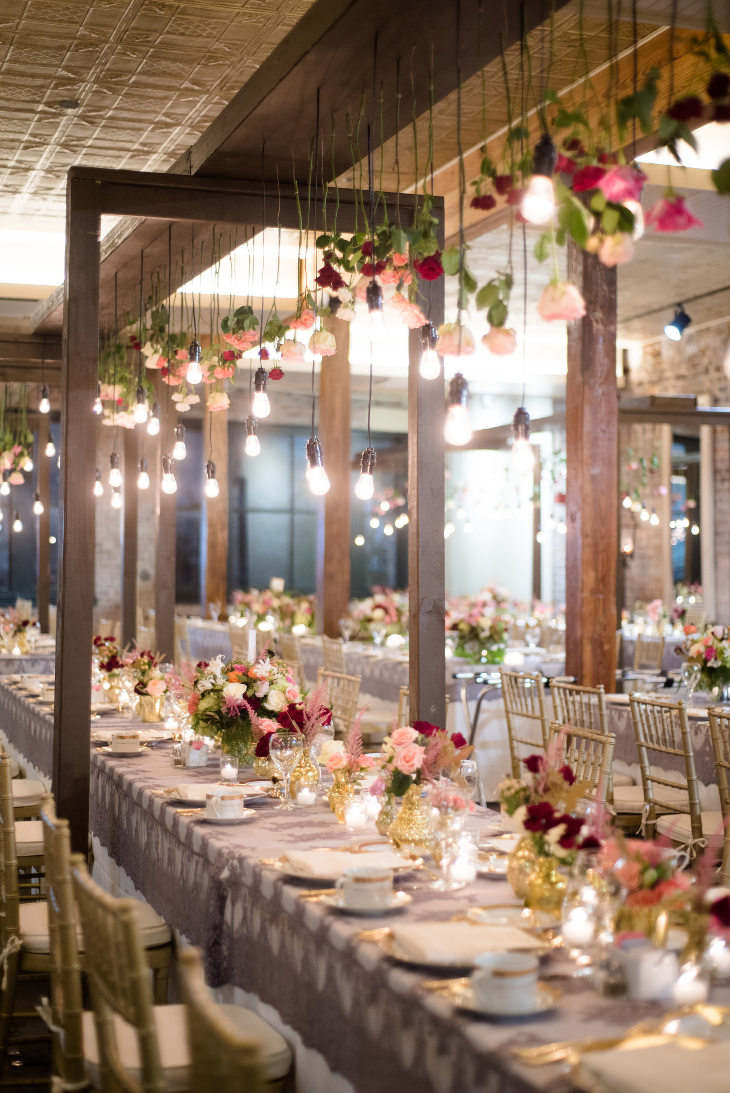 long wedding tables with lace table cloths and suspending roses overhead with hanging lightbulbs