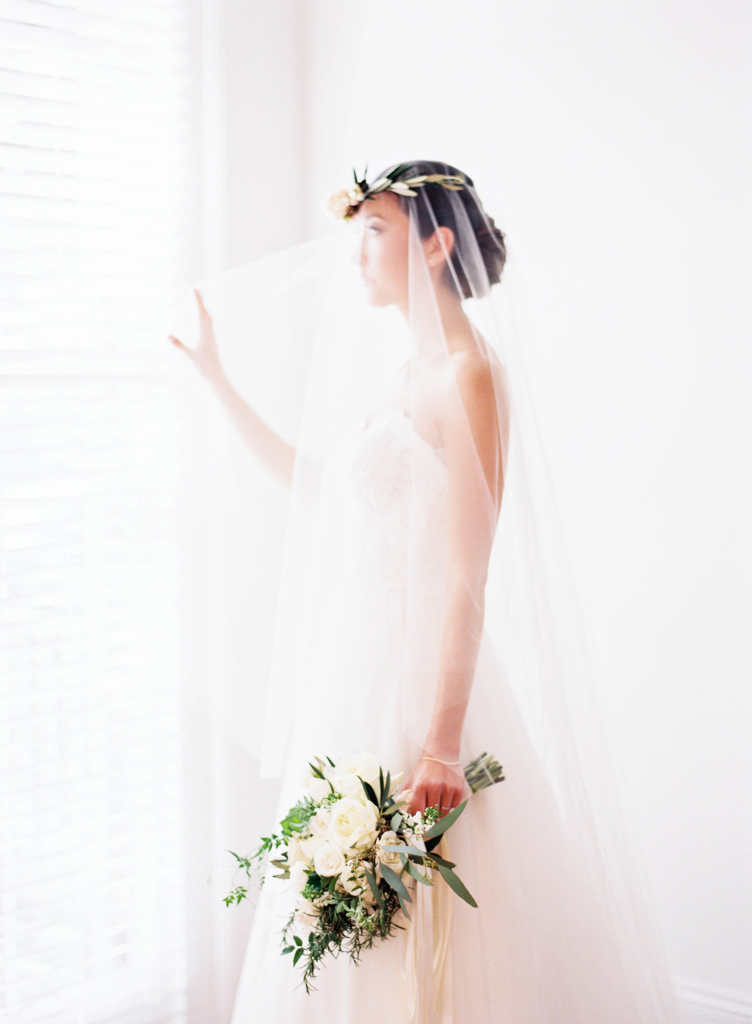 bride in wedding dress with floral head wreath and long sheer veil holding bouquet and looking out the window