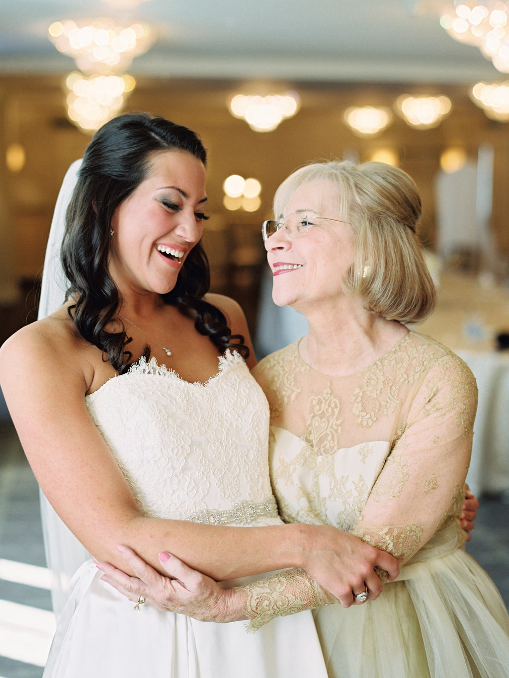 Bride and her mom hug in their beautiful dresses both with lace on them and delicate detailing