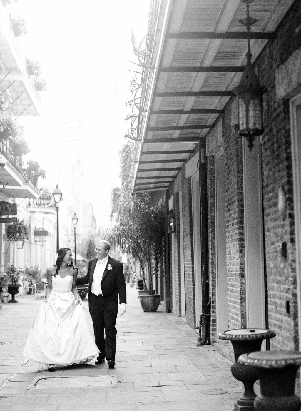 black and white photo of the bride and groom walking down a street in the French Quarter in New Orleans next to a brick wall