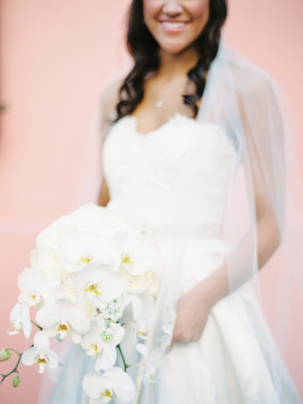 Close up photo of a bride in her wedding gown with a white orchid bouquet