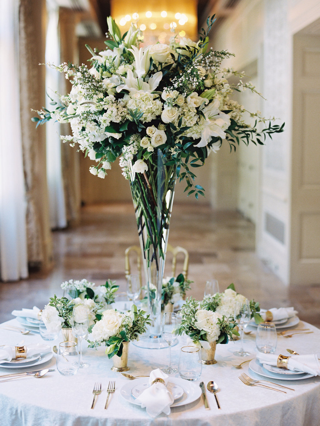 Tall white and green floral arrangement in the middle of a round table with a white table linen set for the wedding reception
