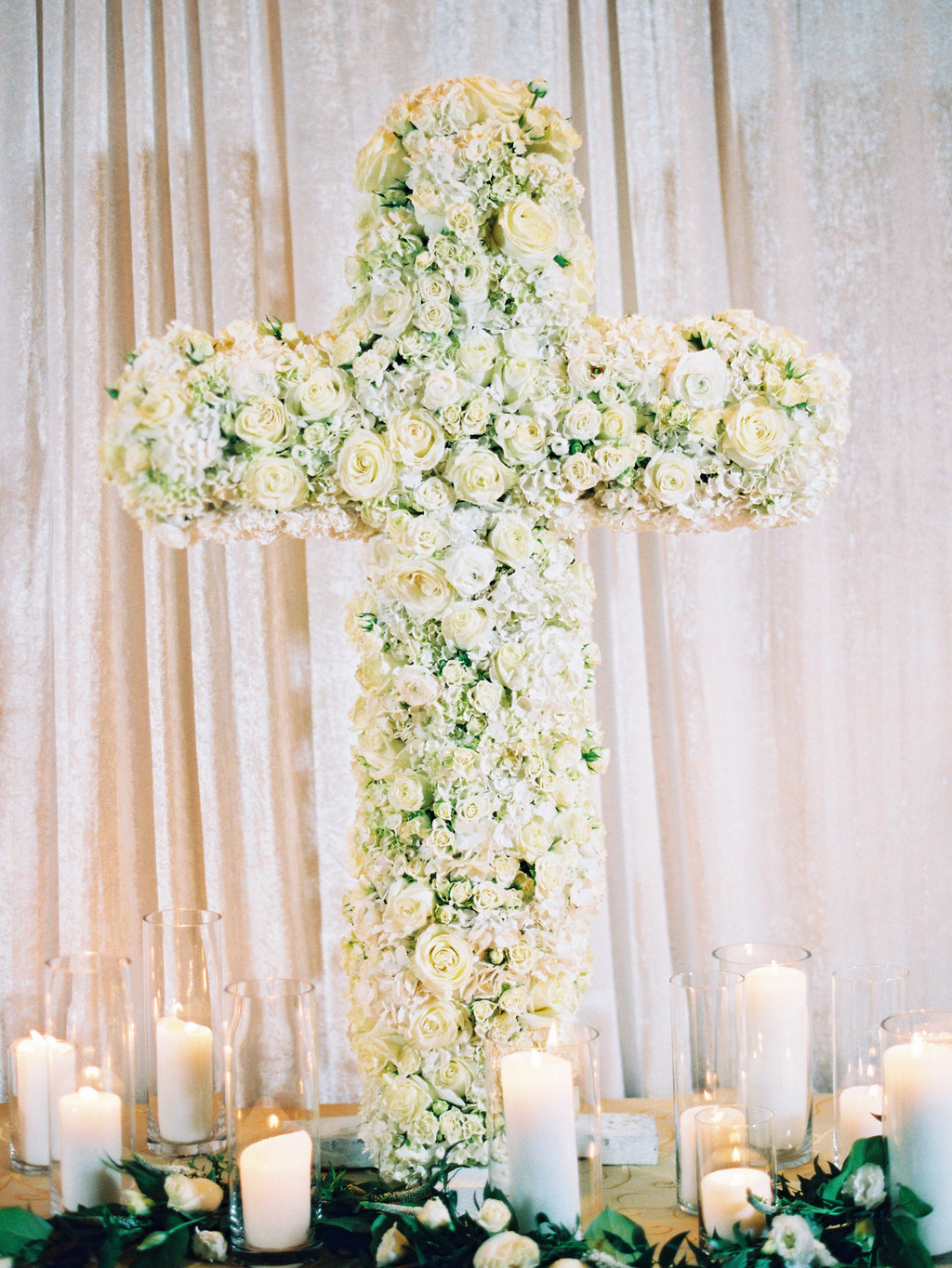 Cross on a table made out of white roses and small white flowers with candles lit around the cross