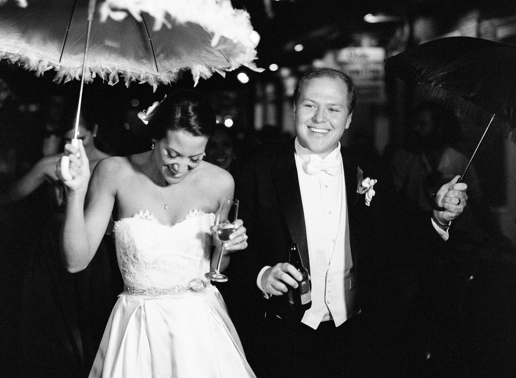 Black and white photo of bride and groom second lining dow the French Quarter with a white and black umbrella with feathers on it