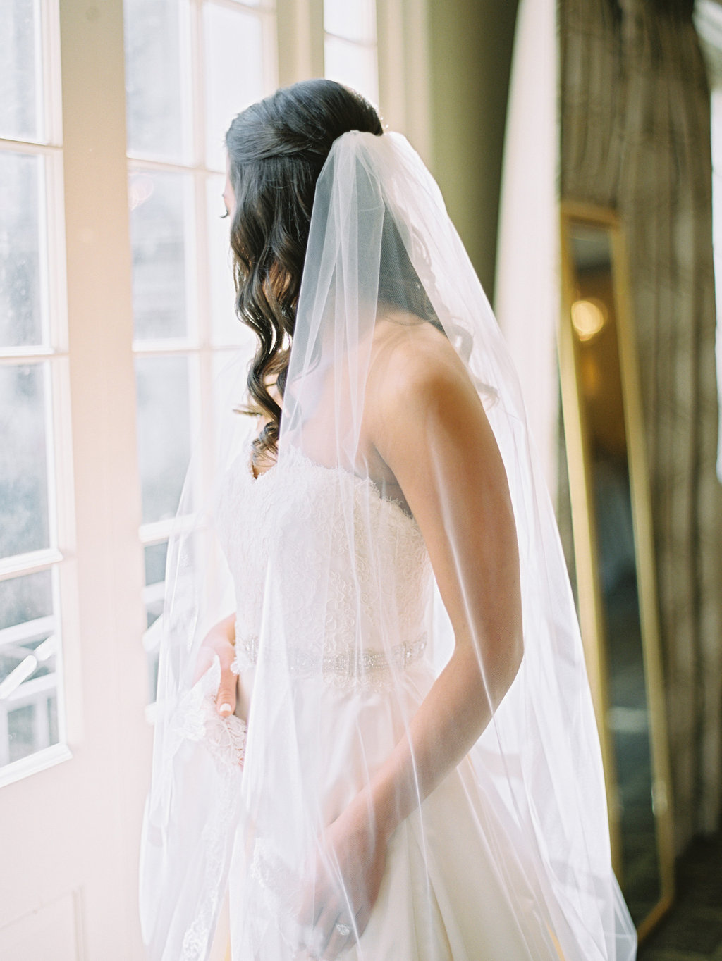 White bridal gown with a beaded gown, and a long sheer veil going down the brides back