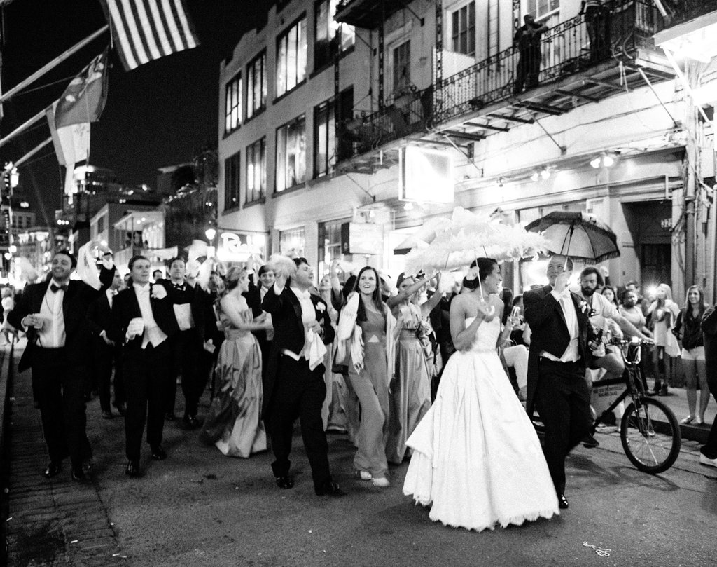 Wedding Party Second lining dow the french quarter with umbrellas and hanker-chiefs