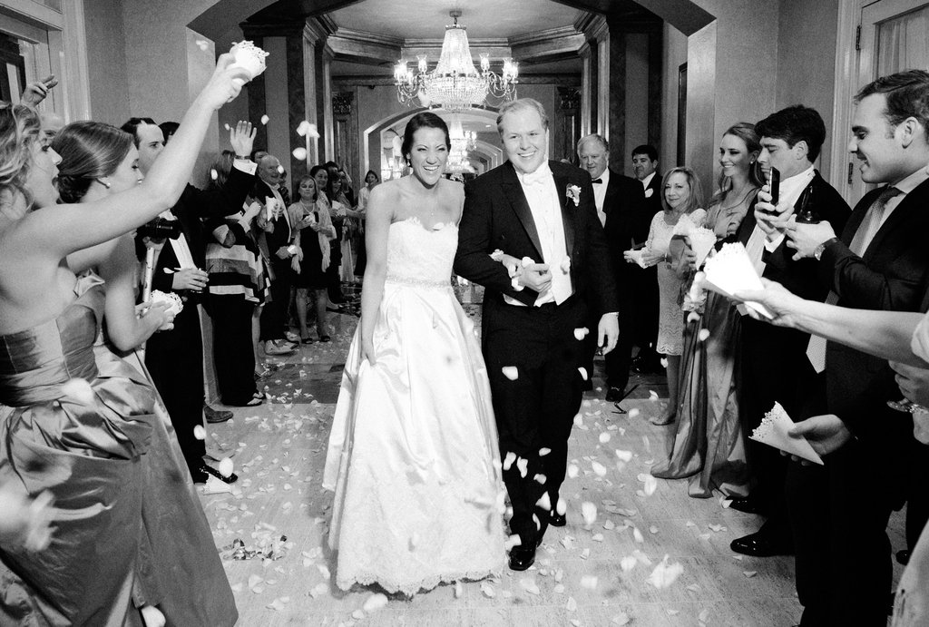 Bride and groom getting sent off at their wedding with the guests throwing white rose petals on them