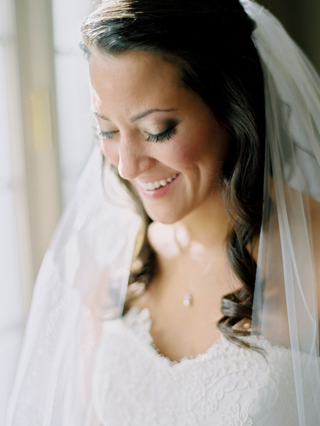 Bride looking down in her wedding dress with her veil over her shoulders on to her lace wedding dress
