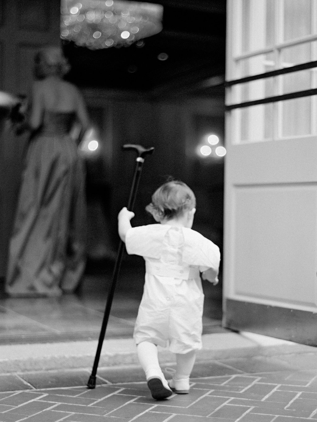 baby at a wedding in a white smocked outfit dancing with a black walking cane