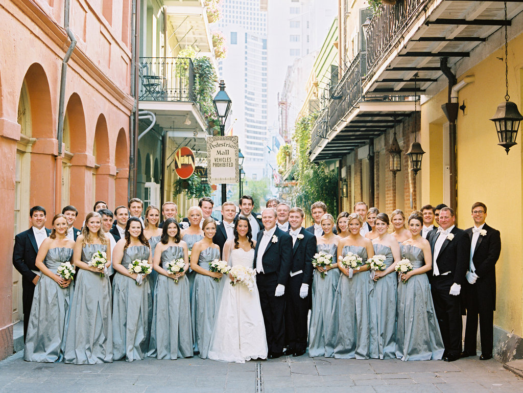Wedding party pose in the french quarter next to a peach and yellow wall