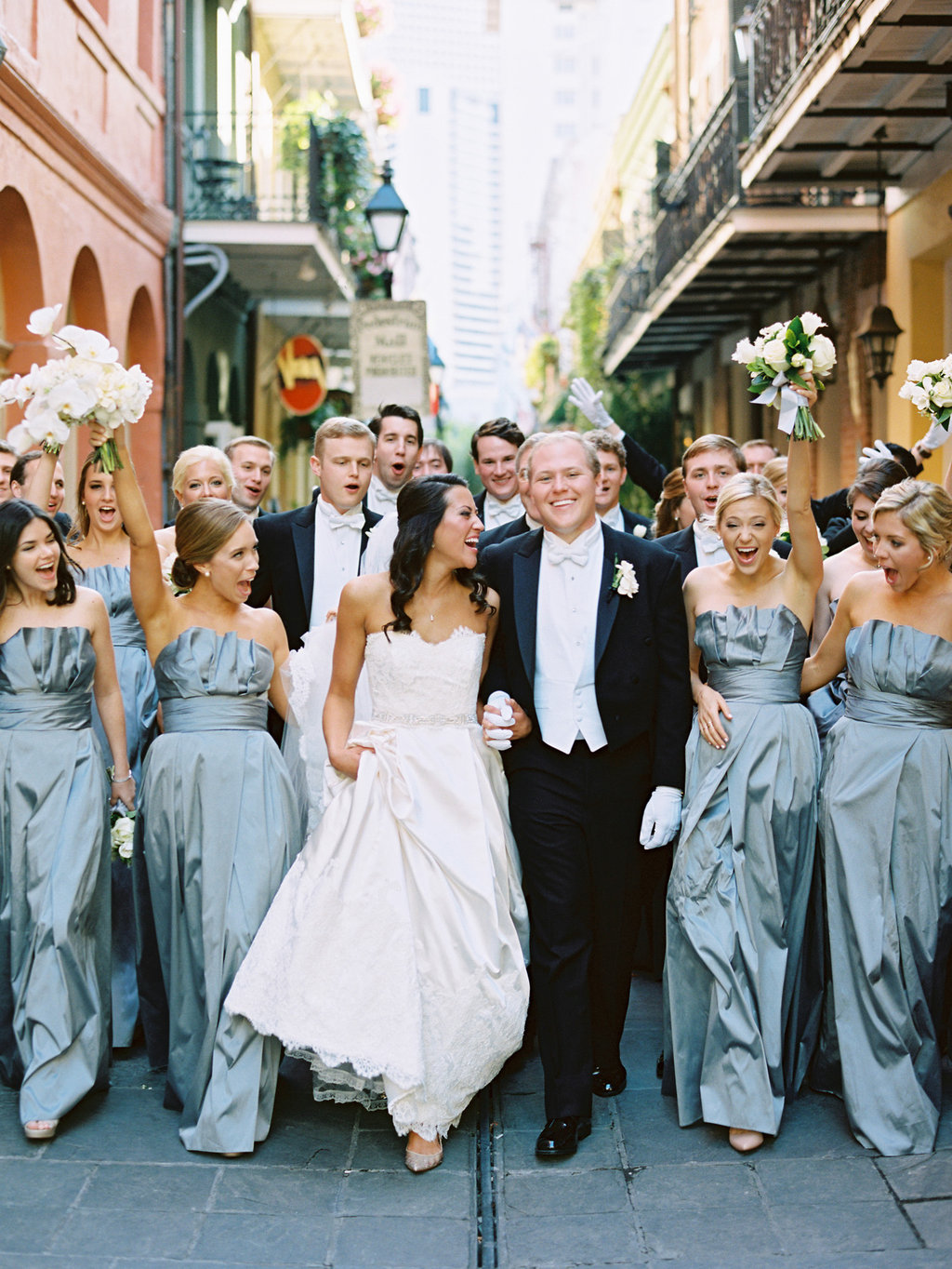 bridal party in light blue strapless dresses cheering on the bride and groom in the French Quarter in New Orleans