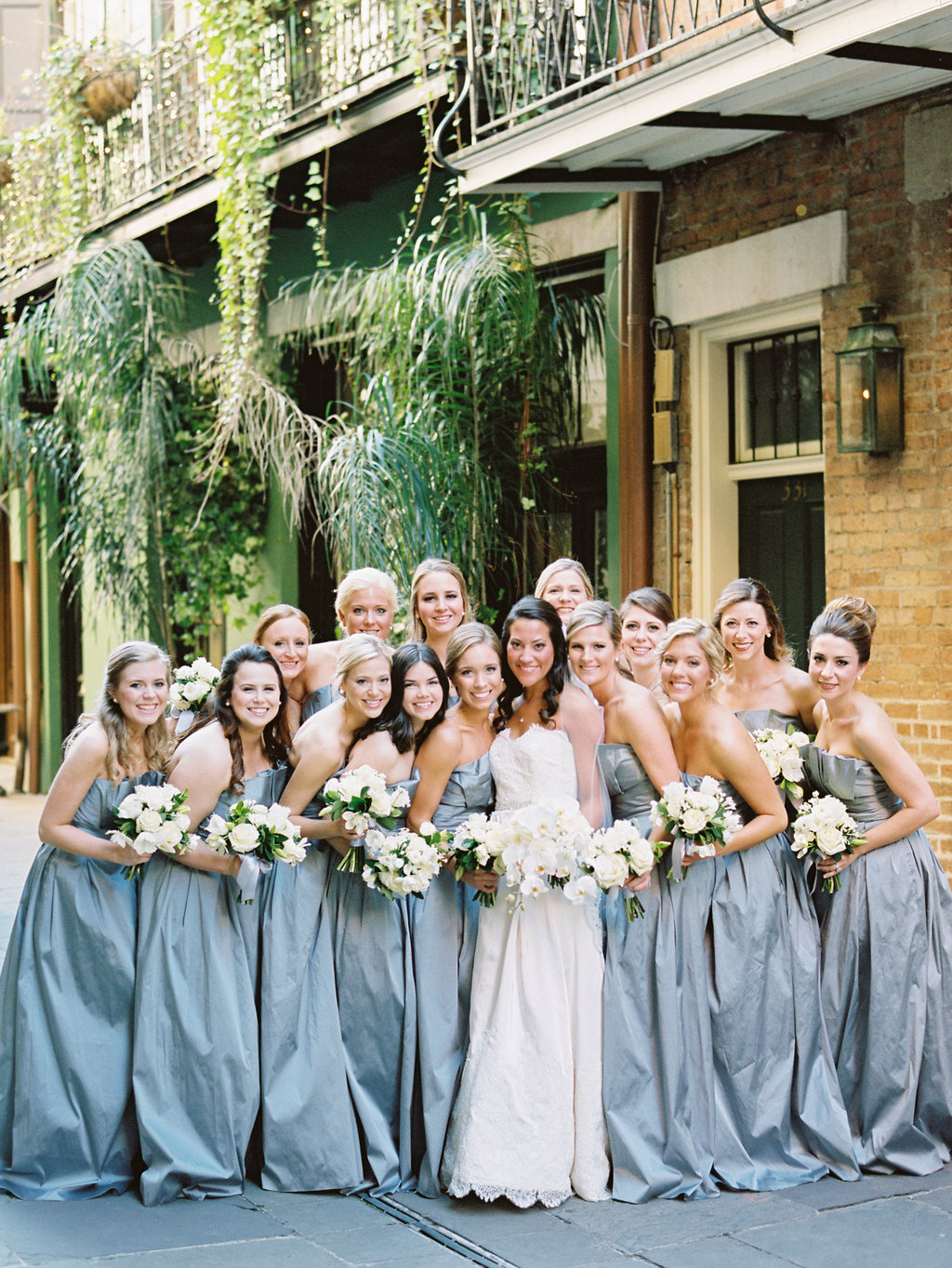 Bridal party huddled around the bride with white flowers in the French Quarter