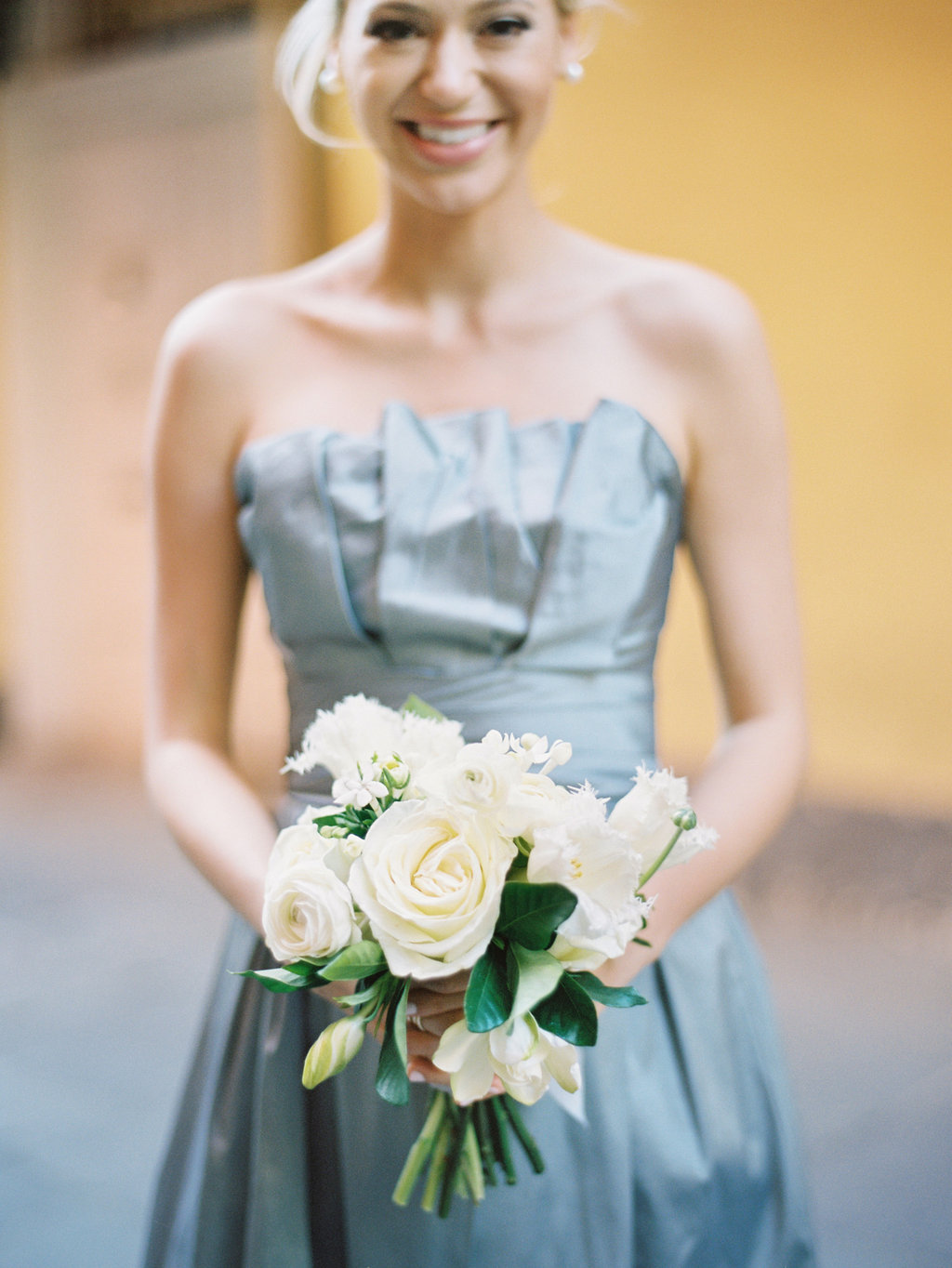 Bridesmaid in a strapless light blue dress and white roses and greenery bouquet