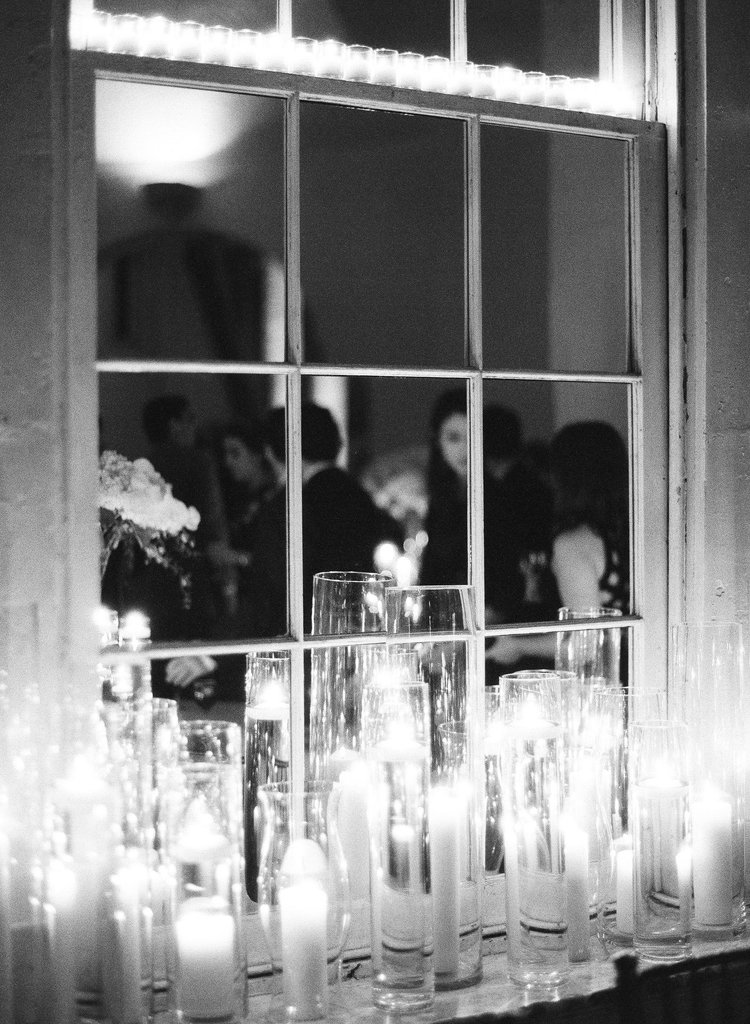 candlelight reflecting in a mirrored window at a wedding reception at night