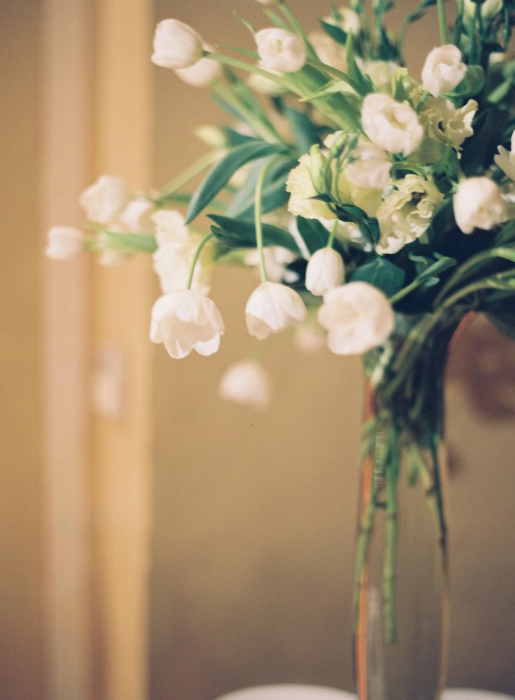 closeup of white tulips and white ranunculus floral centerpiece arrangement