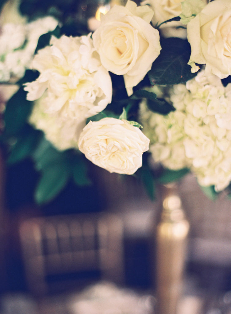 closeup of white floral arrangement and gold vase
