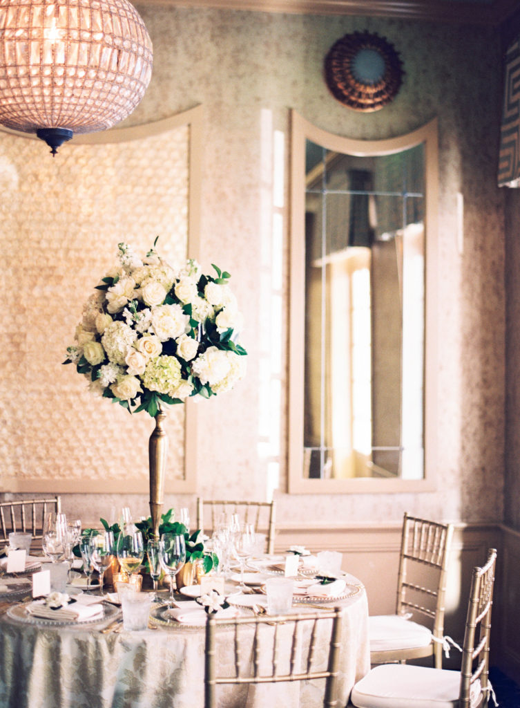 table setting wiht a tall white and green floral arrangement under a round chandelier