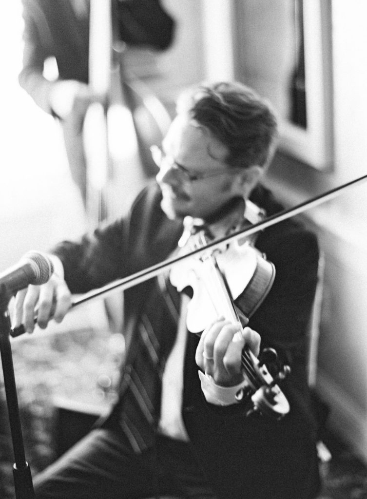 a violinst with glasses playing his instrument as part of a jazz quartet at a restaurant