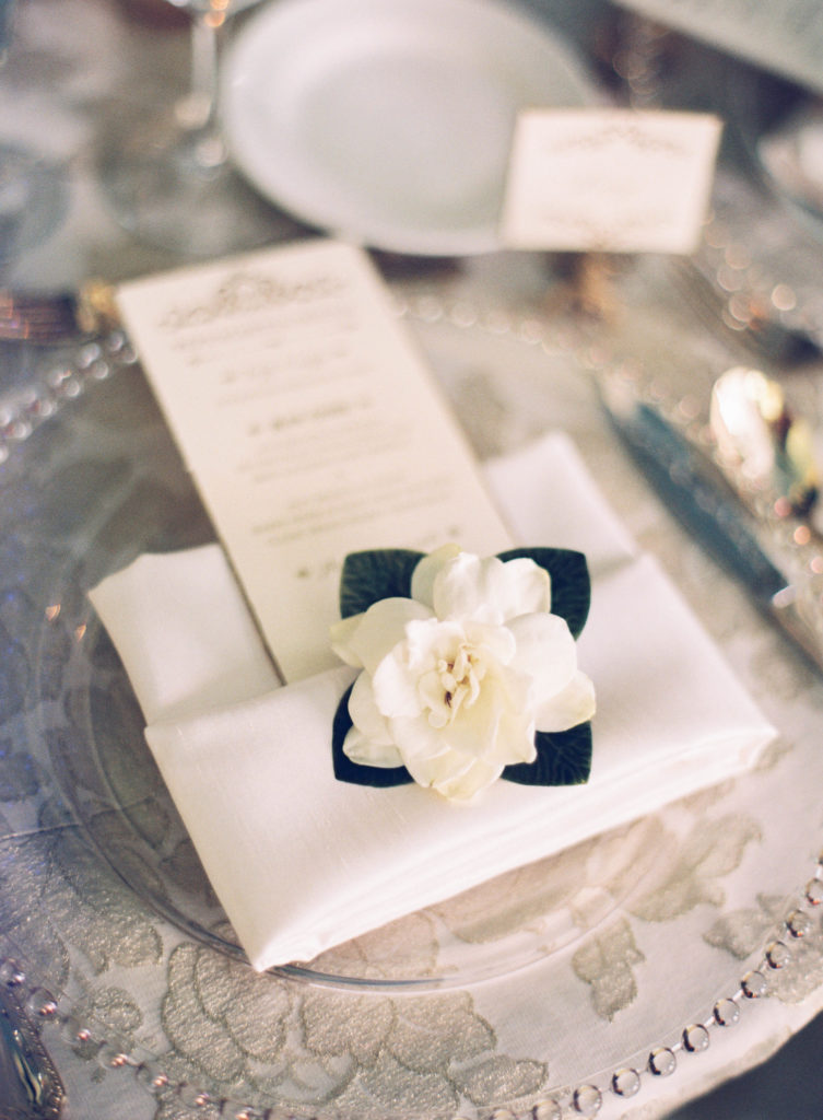 closeup of gardenia flower on a napkin folded with a long menu tucked inside at a place setting for dinner