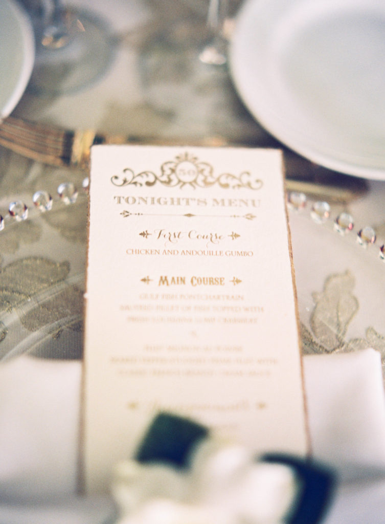long tea length menu with gold lettering featuring the menu of what is being served for dinner