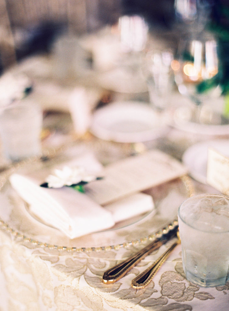 closeup of place setting with gold linen tablecloth and a gardenia flower