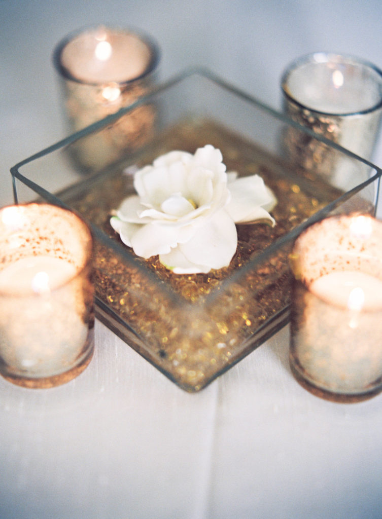 floating gardenia blossom in a square vessel surrounded by four votive candles