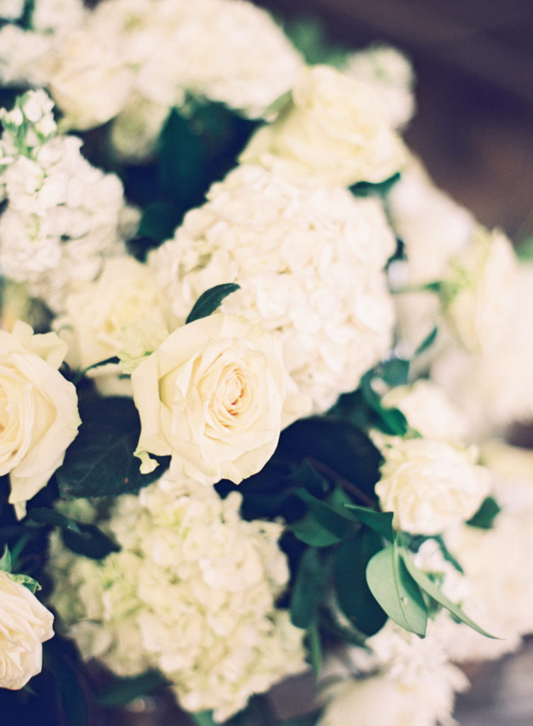 white hydrangea, white roses, and greenery in a floral arrangement