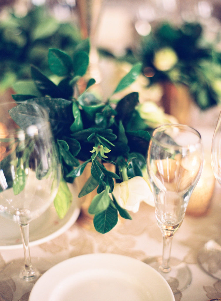 old fashioned champagne flutes with gardenia flowers on a table set for dinner