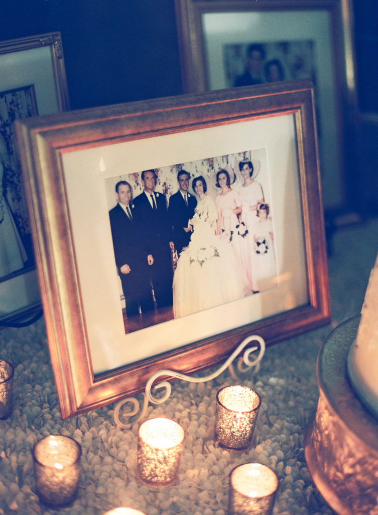 family portrait of a wedding from fifty years ago in a gold frame on a table with votive candles around