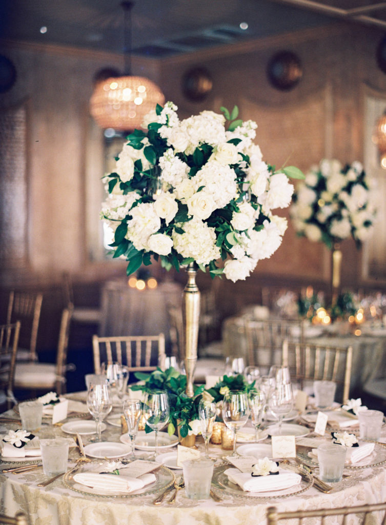 white hydrangea, white roses, and gardenia floral arrangement on a gold vase on a white and ivory table set for dinner