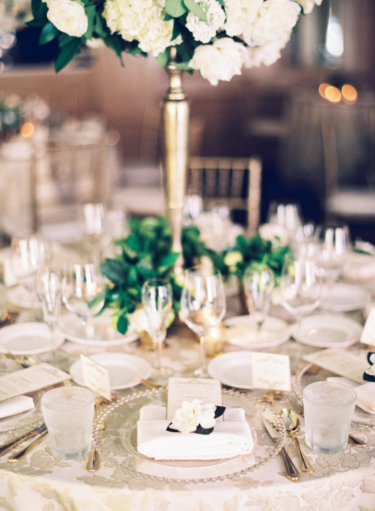 white gardenia on a place setting at a dinner table with white and gold details