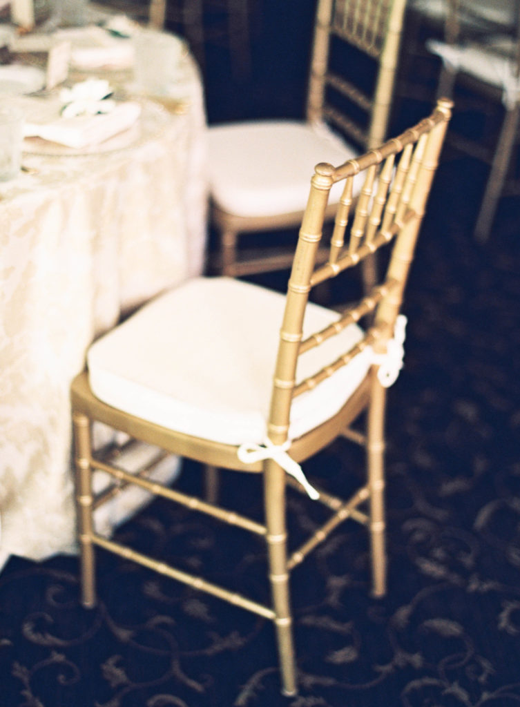 gold chiavari chair with ivory cushion at a dinner table in a room with dark patterned carpet