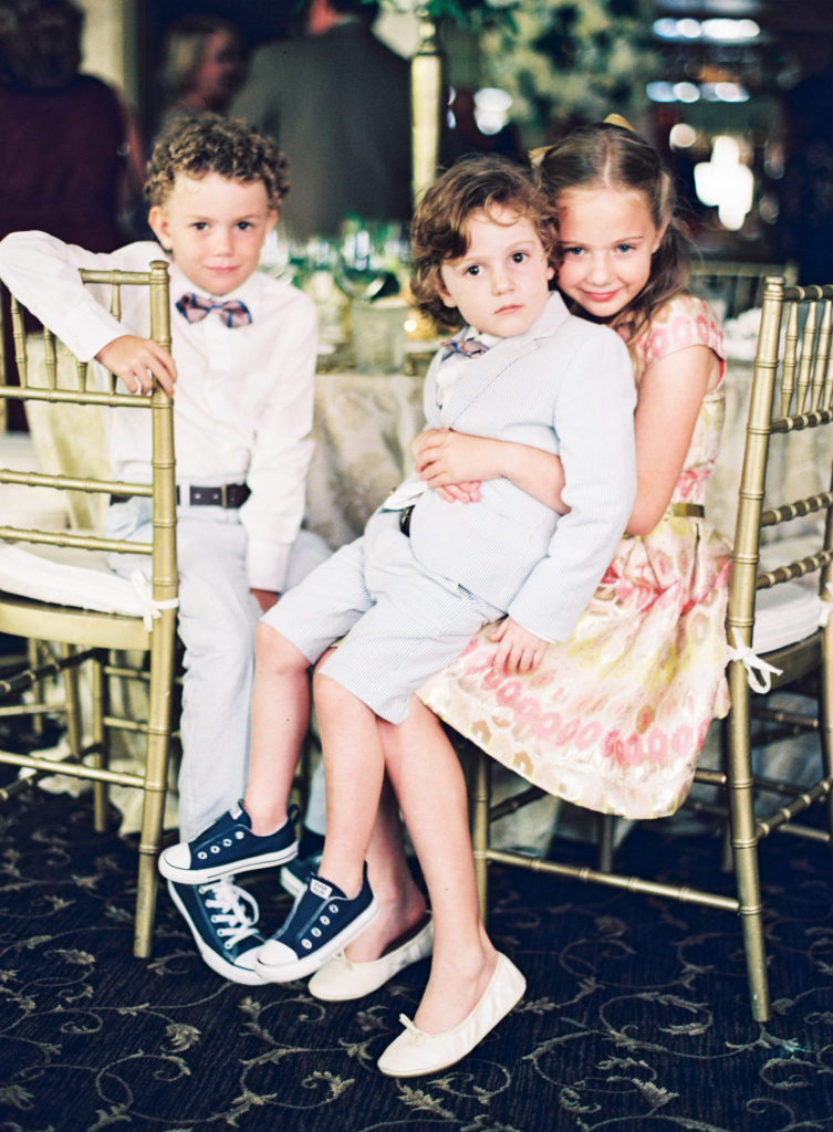 three children dressed in church clothes sitting in gold chiavari chairs at a restaurant looking at the camera
